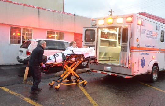 Paramedics from Lifecare Ambulance move a patient from the Econo Lodge in December of 2016 after an apparent drug overdose.