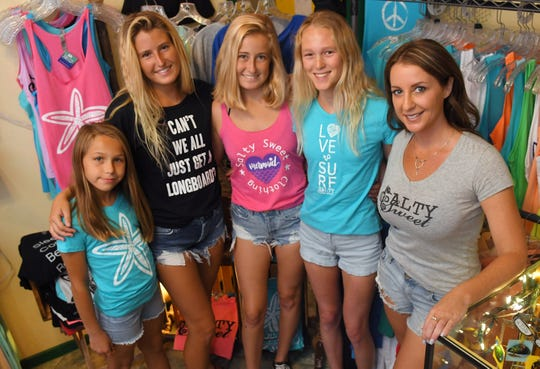 At right, Crystal Cooper, owner and founder of Salty Sweet, poses with, left to right, Grier Hensley, 9, surfing sisters Makaya and Kialani McCutchan, and surfer Sarah Stotz,16, at Barefoot Designs in Cocoa Village, wearing Salty Sweet shirts, which help fund the annual Salty Sweet & Barefoot Designs Pro/Am Surf Contest in Cocoa Beach, October 5th. Barefoot Designs, owned by Barbara Bumgardner, is a host sponsor.
