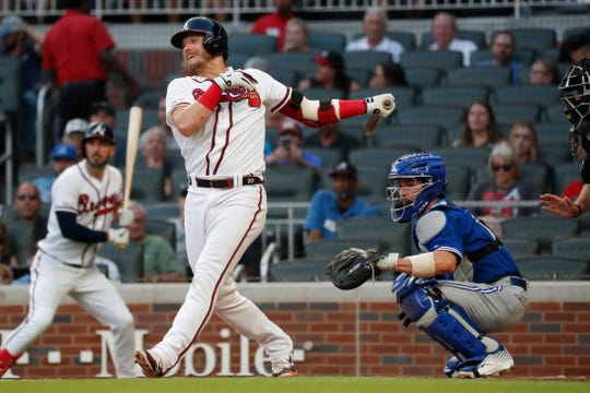 Atlanta Braves third baseman Josh Donaldson (20) drives in a run with a base hit as Toronto Blue Jays catcher Beau Taylor (72), now back with the Oak;and A's, watches during a baseball game Tuesday, Sept. 3, 2019, in Atlanta.
