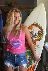 Surfer Makaya McCutchan  poses at Barefoot Designs in Cocoa Village wearing a Salty Sweet shirt. Sales of the clothing line which help fund the annual Salty Sweet & Barefoot Designs Pro/Am Surf Contest in Cocoa Beach, October 5th. Barefoot Designs, owned by Barbara Bumgardner, is a host sponsor.