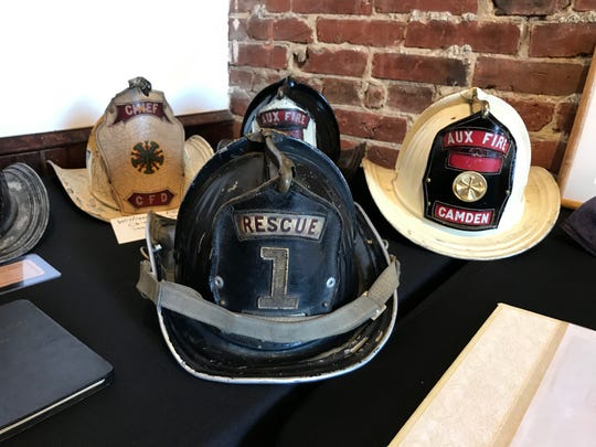 Historic Camden Fire Department helmets sit on a table at FireWorks, a former firehouse-turned-art gallery in South Camden. The helmets were part of a display of historical items from the department's 150 years of service.