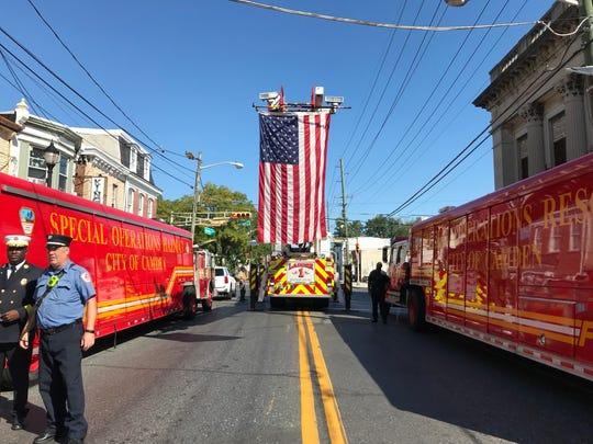 An American flag, held aloft by a Camden Fire Department ladder truck, flies over Broadway on Wednesday.