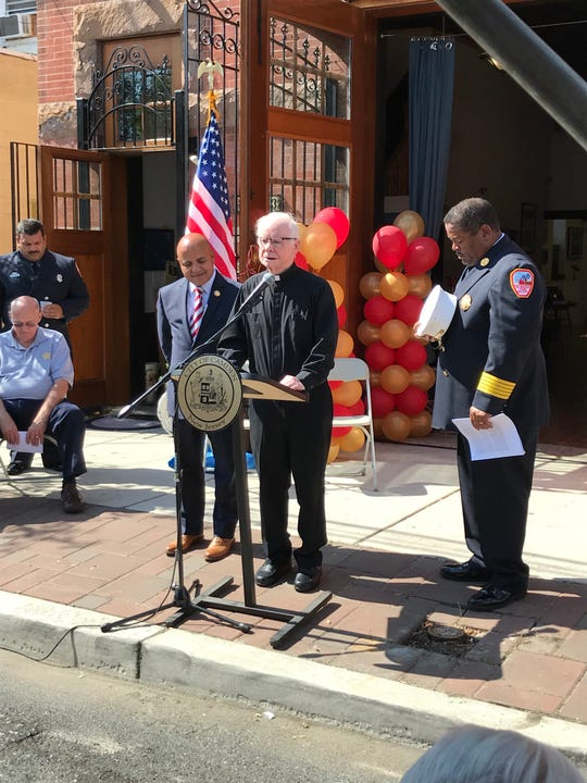 Msgr. Michael Doyle of Sacred Heart Church offers a prayer Wednesday for Camden's firefighters as Mayor Frank Moran (left) and Chief Michael Harper bow their heads. The prayer was part of a celebration of the department's 150th anniversary.