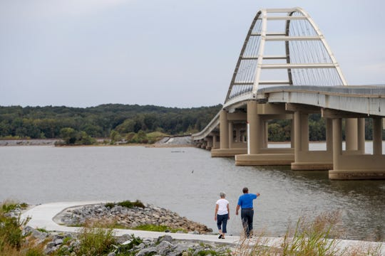 """Mike and Debbie Rust, locals in Canton since 2003, walk down a trail to the waters edge, pointing at different points on the bridge after the ribbon cutting ceremony for a multi-use trail and honorary opening of the new bridge across the Cumberland River at Lake Barkley Bridge in Canton, KY., on Wednesday, Sept. 25, 2019. The Rusts spoke about memories of the old bridge both their experiences of driving by the mirrors of other drivers and how when Mike used to go fishing """"when we floated under the bridge and cars passed above you, you could feel little bits of concrete fall onto you."""""""