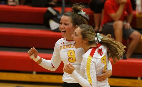 Carlisle senior Meredith Hoffman and junior Sydney Berg celebrate a point in the second game. Carlisle lost in four games to Carroll in a Sept. 24 Raccoon River Conference match in Carlisle.