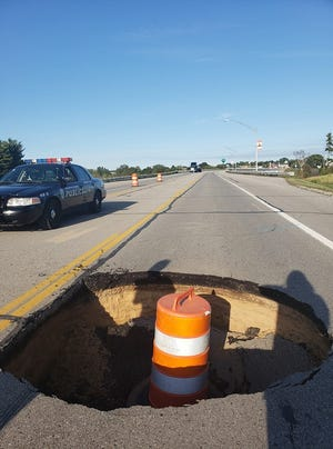 A large hole in the road forced authorities to close a portion of U.S. 2 in Manistique, Michigan on Wednesday, Sept. 23, 2019.