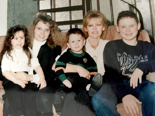 Debbie Pickworth, left, holds her daughter Amanda on her lap. Beside her, Pickworth's mother, Sharon Sutter, holds her grandson Sean and her youngest son, Randy.  Sharon Sutter died of lung cancer in 1997 at the age of 49. Debbie Pickworth also has the disease.