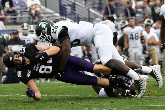 Northwestern wide receiver Bennett Skowronek (88) is tackled by Michigan State linebacker Brandon Bouyer-Randle on Saturday in Evanston, Illinois.