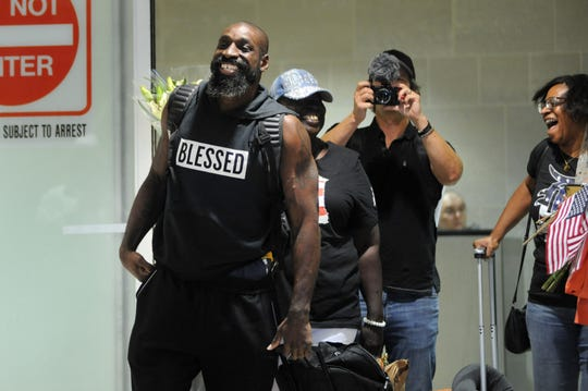 Detroit native Wendell Brown, left, who spent three years in a Chinese prison, arrives at Detroit Metro Airport, Wednesday, Sept. 25, 2019 in Romulus.