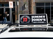 In this Feb. 6, 2019, photo, Tyler Schwecke, a delivery driver for Jimmy John's, makes a delivery in Las Vegas. The parent company of Arby's and Buffalo Wild Wings is buying Jimmy John's Sandwiches.