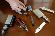 In this Tuesday, April 10, 2018 file photo, Marshfield High School Principal Robert Keuther displays vaping devices that were confiscated from students in such places as restrooms or hallways at the school in Marshfield, Mass.