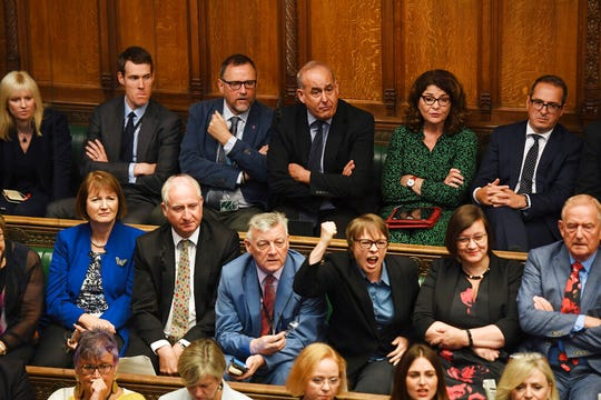 In this handout photo provided by the House of Commons, opposition MP's look on as Britain's General Attorney Geoffrey Cox speaks in Parliament in London, Wednesday, Sept. 25, 2019. British lawmakers returned to the House of Commons on Wednesday, venting their pent-up anger over Prime Minister Boris Johnson's failed attempt to suspend Parliament and warning that democracy itself is under threat from the government.