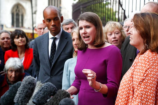 Britain's Liberal Democrat leader Jo Swinson, center, speaks with the media as she arrives at Parliament in London, Wednesday, Sept. 25, 2019.