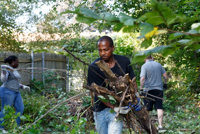 Richard Gray Jr. helps clear out branches Sept. 20 during a Regent Park Community Association clean-up day in an alley in the northeast Detroit neighborhood.