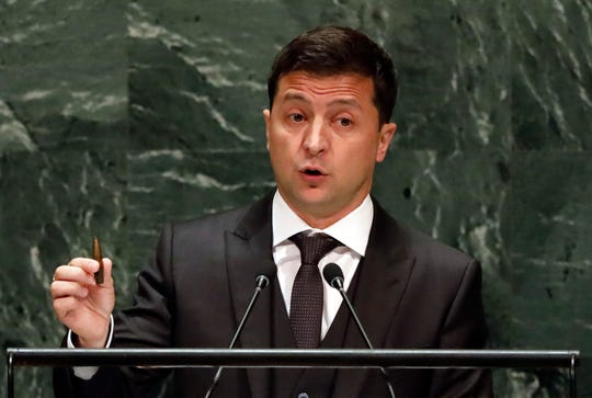 Ukraine's President Volodymyr Zelenskiy holds a bullet as he addresses the 74th session of the United Nations General Assembly, Wednesday, Sept. 25, 2019.
