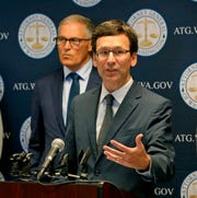 """Washington state Attorney General Bob Ferguson, right, announces a lawsuit challenging Trump's use of Washington military project funding to pay for border wall in this Thursday, Sept. 19, 2019, file photo. New Endangered Species Act rules from the Trump administration which, for the first time allow officials to consider how much it would cost to save a species, were called """"death by a thousand cuts"""" for the law by Ferguson."""