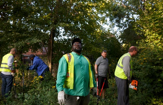 President of the Regent Park Community Association DeShawn Hurt, center, looks up at trees that need to be cleared out of an alley in the northeast Detroit neighborhood on Sept. 20.  The long-maligned 48205 ZIP code is seeing less crime and more active block clubs in recent years.