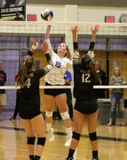 Carolyn Bovaird of Horseheads goes for the kill as Corning's Madalyn Bouton (14) and Kaitlyn DiNardo (12) try for the block Sept. 24, 2019 at Corning-Painted Post High School.