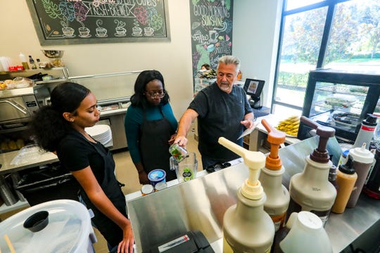 Sal Basile works with new employees during a training session last week at Rise & Grind Cafe in Gateway.