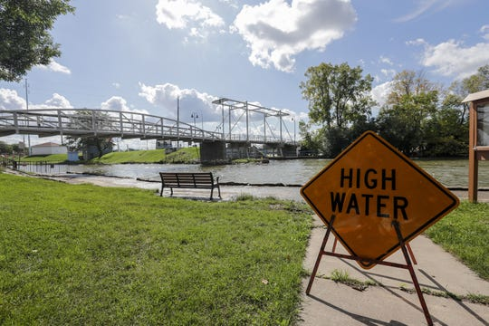 A sign warns of high water on the Fox River Wednesdayat Voyageur Park in De Pere. Record rainfall has forced the Army Corps of Engineers to increase the amount of water flowing from Lake Winnebago through dams on the Lower Fox River to prevent upstream flooding.