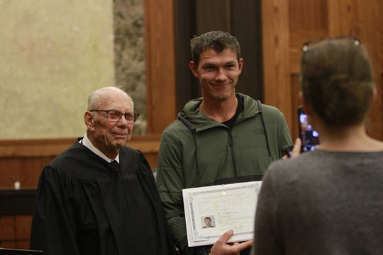 Ivan Yarmolich, right, takes advantage of a photo opportunity with U.S. Magistrate Judge Robert Holter at a naturalization ceremony Wednesday in Great Falls.
