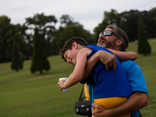 """I am so proud of you,"" Ken Galyon says as he embraces his 9-year-old son Makai Galyon, who competed in the boys elementary 2k race at the fifth annual Junior Colonel Cross Country district championship on the site of the former Municipal Golf Course in Henderson, Ky., Tuesday evening, Sept. 24, 2019. Makai, a Spottsville Elementary student, finished 16th out of 69 competitors."