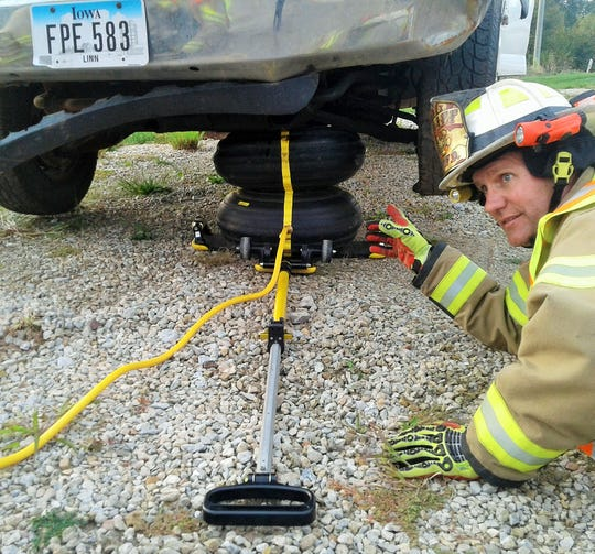 A twin-chambered air bag inflated beneath a vehicle can lift it quickly off an accident victim, as demonstrated here by Chief Glen Heims of the Swisher department.