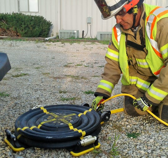 Chief Glen Heims attaches an air hose to the lift air bag prior to sliding it beneath a vehicle during a training exercise by Jefferson Monroe Fire Department.