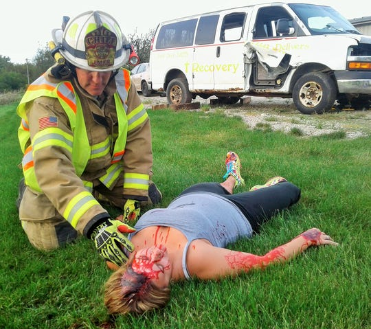 EMT/Paramedic Crystal Shramek portrays an accident victim during extraction training recently by the Jefferson Monroe Fire Department. Chief Glen Heims attends to her here.