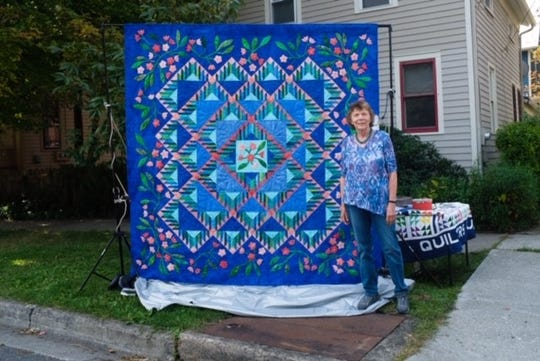 Tompkins County Quilter's Guild member Sherry Haefele stands beside a quilt that will be raffled off at the Tompkins County Quilter's Guild show in October.