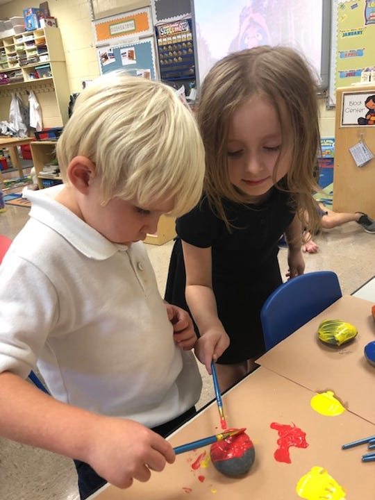 Cannon Fesmire and Bridgette Bartlett paint peace rocks at Nova Early Learning Center in celebration of International Day of Peace.