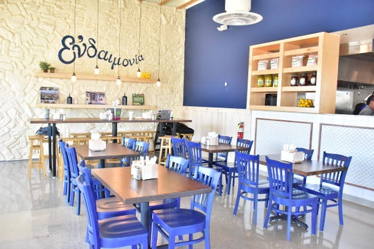 Natural light and pops of bright blue provide a warm, inviting eating area in Taziki's.