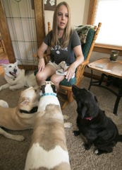 Gracie's Dog Haven owner Sheila Hall-Gabriel, surrounded by (from left) Kai, Romeo, Karma and Anna, talks about caring for the senior dogs at her Oceola Township home Tuesday, Sept. 24, 2019.