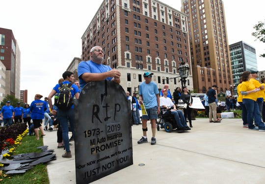 People, including health care worker Casey Leonard, left, of Adrian, Michigan, protest at the State Capitol in downtown Lansing, Wednesday, Sept. 25, 2019, during a rally organized by the Michigan Auto Insurance Promise. They were protesting the recently passed auto insurance reform bill. [AP PHOTO/MATTHEW DAE SMITH/Lansing State Journal]