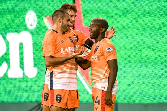 Lansing Ignite's Elma Nfor, right, celebrates his goal with teammates, from left, Pato Botello Faz and Brandon Fricke during the first half on Tuesday, Sept. 24, 2019, at Cooley Law School Stadium in Lansing.