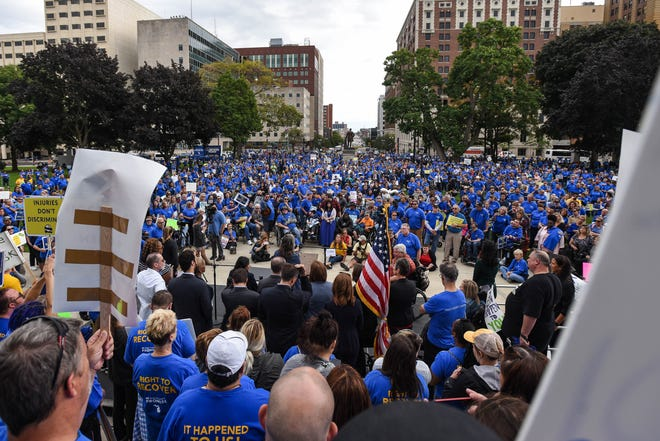 People protest at the State Capitol in downtown Lansing, Wednesday, Sept. 25, 2019, during a rally organized by the Michigan Auto Insurance Promise. They rallied against the recently passed auto insurance reform bill. [AP PHOTO/MATTHEW DAE SMITH/Lansing State Journal]