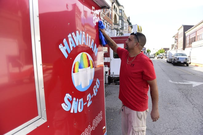 Sean Parsloe of Mount Vernon polishes the outside of his snow cone trailer Wednesday in preparation for the Galion Oktoberfest, which runs Thursday to Saturday.