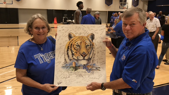 Betty and Chris Luhrs display a poster Tuesday with dozens of autographs from Memphis basketball players past and present.