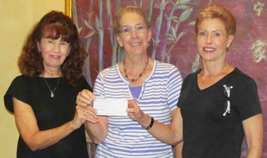 MIFA treasurer Carolyn Burger and president Karen Swanker give a donation to Jan Rich for The Love Of Cats organization