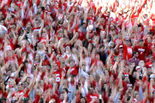 "Students jump up and down to the song ""Jump Around"" at Camp Randall Stadium in Madison."