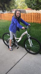 Jenna Kofoed, 11, of South Milwaukee likes her new bicycle which was gifted to her by Cudahy resident Michelle McCormick after Jenna's bike was stolen.
