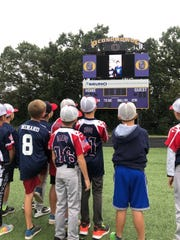 Players from an Oconomowoc Five O's team watch a surprise video from two Milwaukee Brewers.