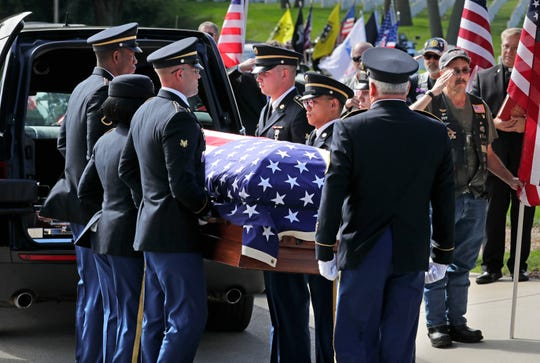 An honor guard moves a casket with the remains of Pfc. Vincent J. Ferrara  who was reported missing on Nov. 14, 1944, in Germany. He was buried at Wood National Cemetery in Milwaukee, Wednesday, Sept. 25, 2019.