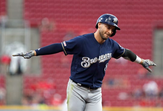 Ryan Braun holds his arms out as he rounds the bases after hitting a solo home run for the Brewers against the Reds in the second inning.