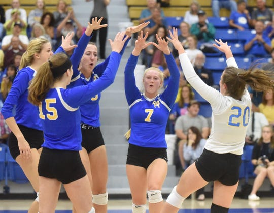 The Mountain Home Lady Bombers celebrate after winning a point against Marion on Tuesday night.