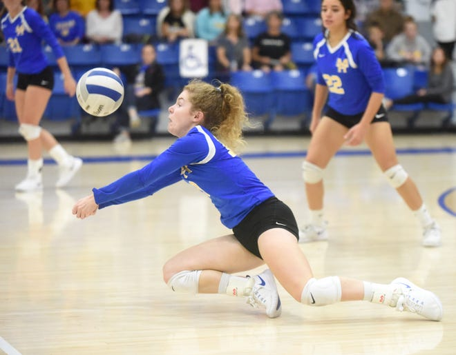 Mountain Home's Grace Beckham dives to receive a serve during the Lady Bombers' three-set sweep of Marion on Tuesday night at The Hangar.
