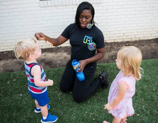Teacher Lea'Neshia Jackson blows bubbles with her students during recess at James Rushton Early Learning Center in Birmingham, Ala., on Thursday, Sept. 12, 2019.