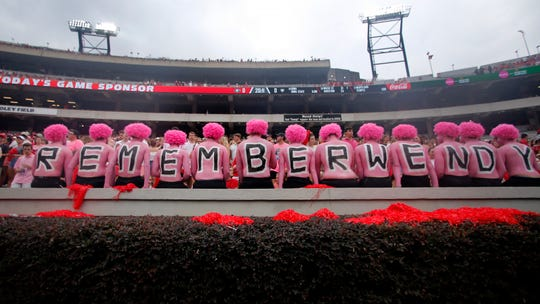 "Georgia fans observe a moment of silence in horror of Wendy Anderson, wife of Arkansas State head coach Blake Anderson before an NCAA college football game Saturday, Sept. 14, 2019, in Athens, Ga. Fans were encouraged to ""pink out"" the stadium for Wendy Anderson who died from breast cancer in August. (AP Photo/John Bazemore)"