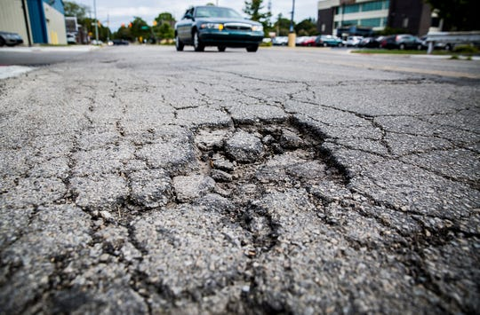 Potholes mar a section of Adams Street in downtown Muncie.
