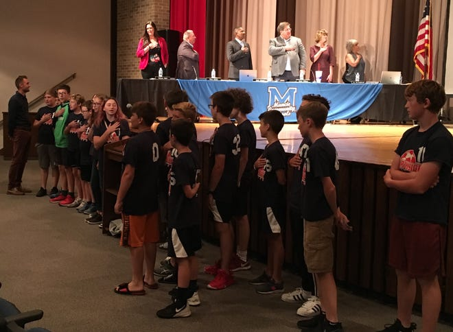 Northside Middle School students and school board members prepare to cite the Pledge of Allegiance at the start of a board meeting on Tuesday night.